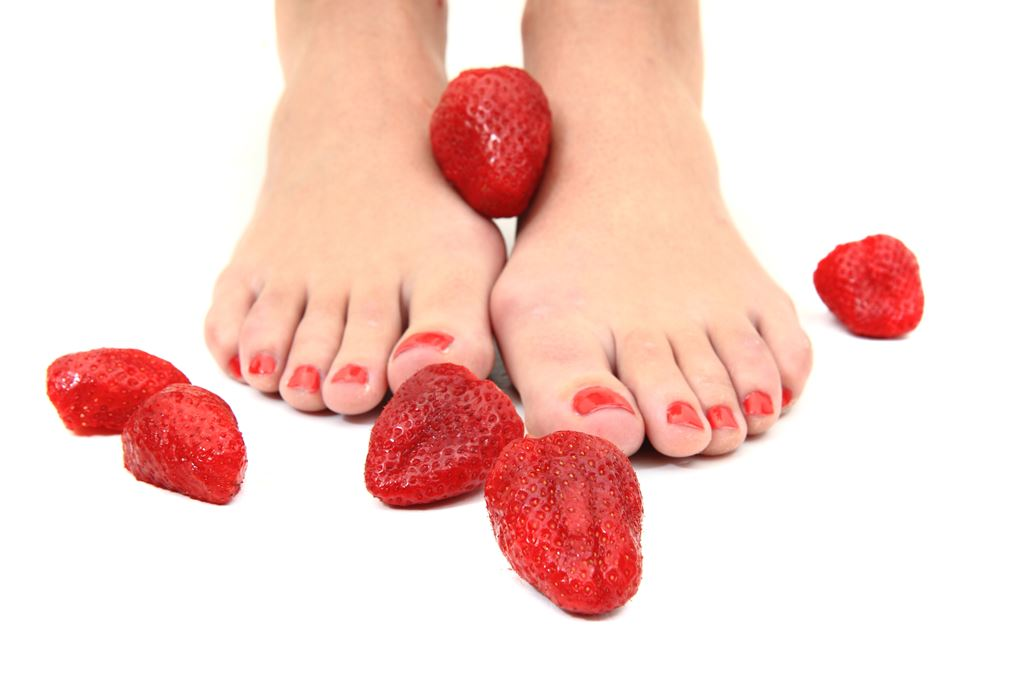 red pedicure surrounded by strawberries