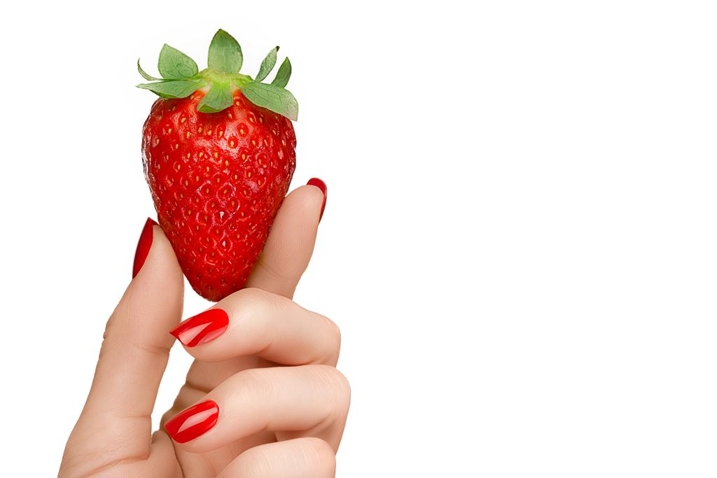 strawberry held by a woman's hand with red fingernails