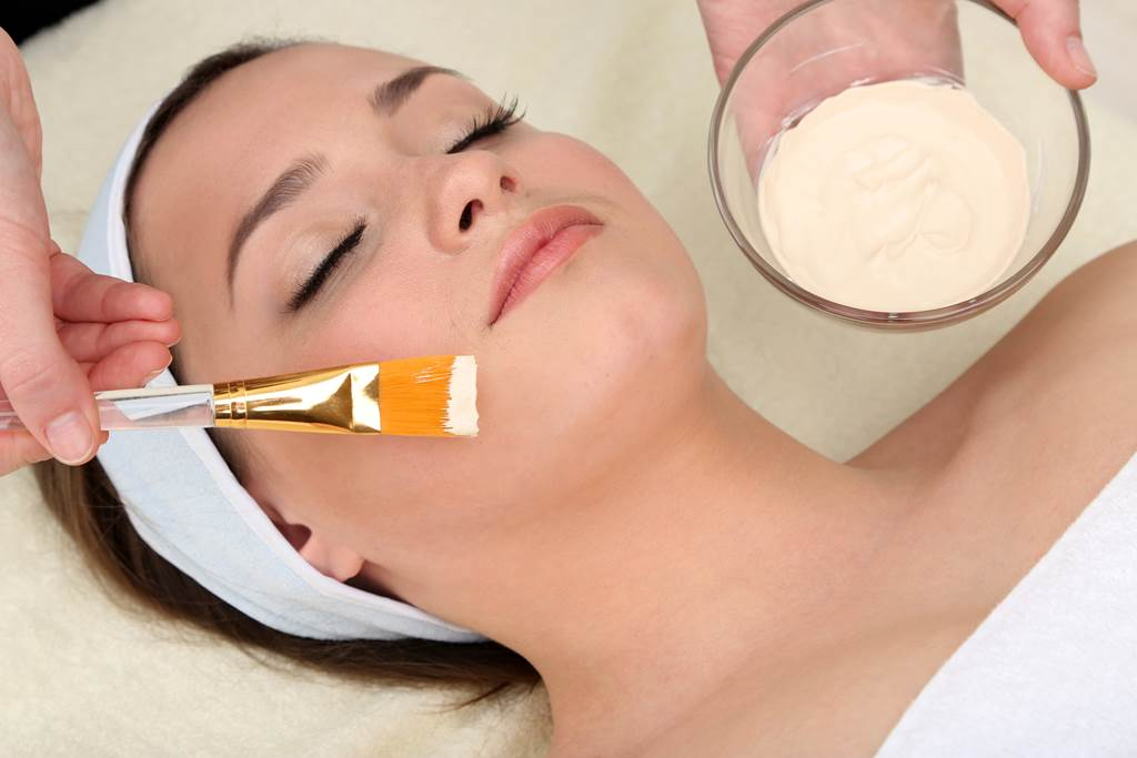 Beautiful young woman in a spa receiving a facial