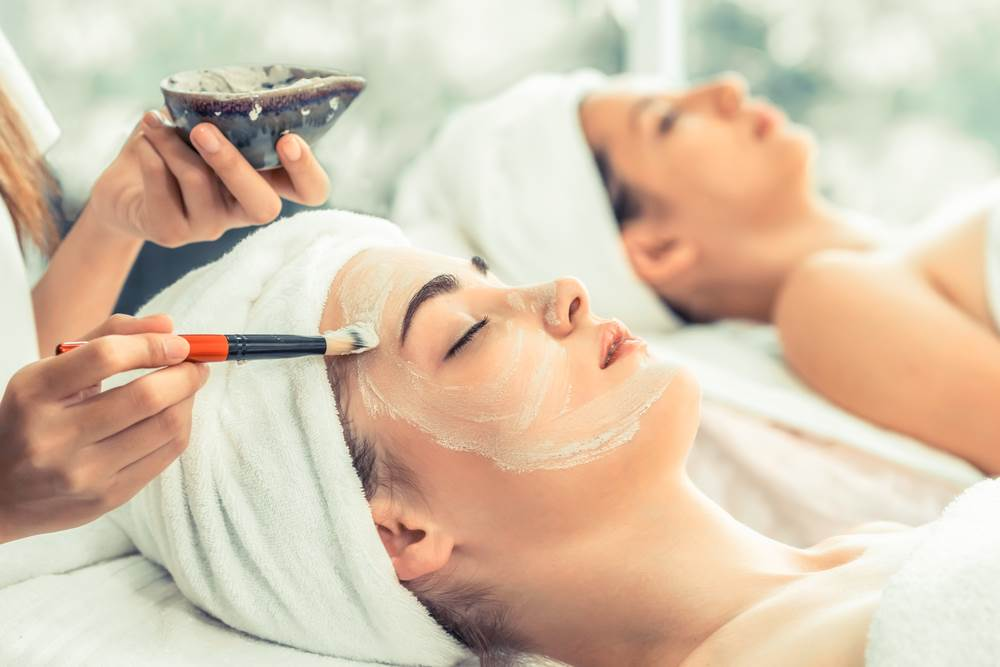 two women getting facial exfolation treatment at a spa
